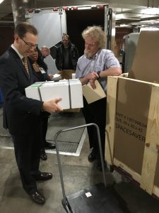 A photo featuring American Folklife Center acquisitions coordinator, Todd Harvey, taking posession of a package containing several rare Woody Guthrie recordings. He and another Library staff member are standing in the loading dock at the Library of Congress. Photo by John Fenn.
