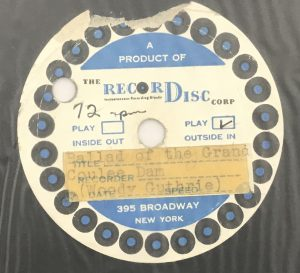 "Close up of label for instantaneous disc recording of ""Ballad of the Grand Coulee Dam"" by Woody Guthrie. Text on typed label reads ""Ballad of the Grand Coulee Dam (Woody Gutherie)""."