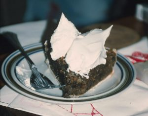 A dark pie wedge with whipped cream on a plate.
