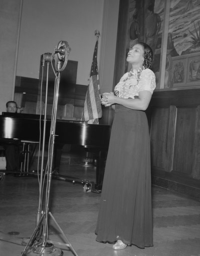 An African American woman sings into a microphone. A man playing a piano can be seen in the background.