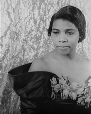 An African American woman wearing a formal dress with a flowered bodice. Head and shoulders portrait.
