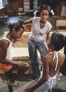 Three African American young women playing a hand clapping game.