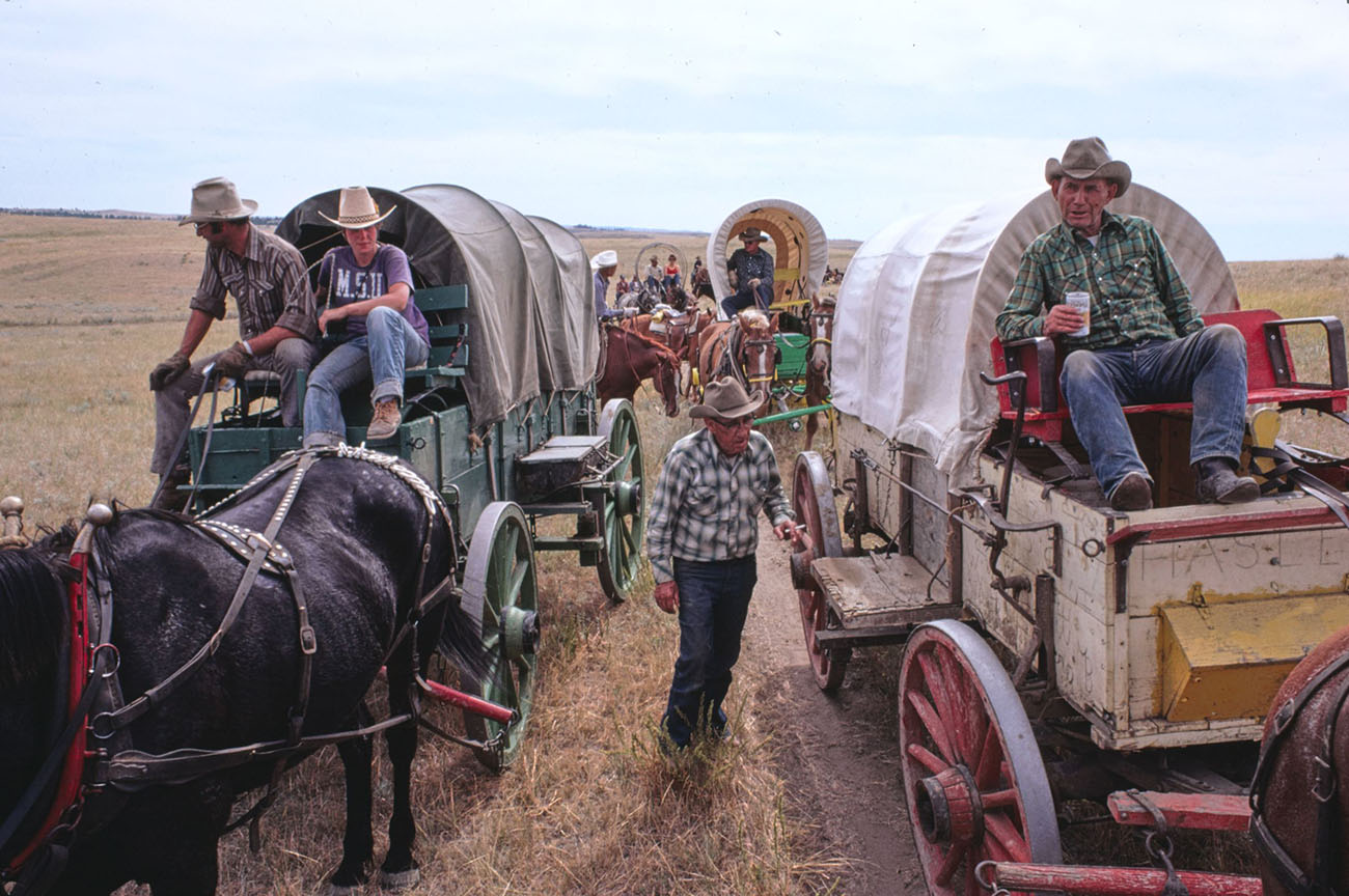 Men and women sitting on or standing by covered wagons that are arranged in a double line. Some horses are visible.