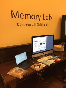 "Picture of a computer station with the words ""Memory Lab: Do-it-yourself Digitization"" on the wall."