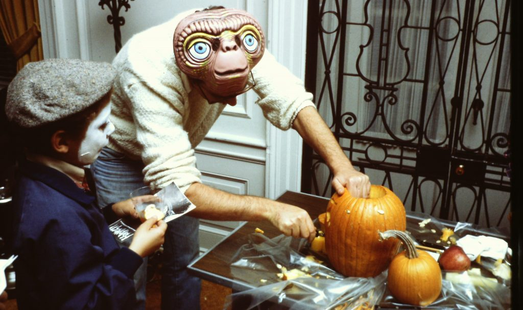 Man in E.T. mask carves a pumpkin while a boy with a painted face watches.