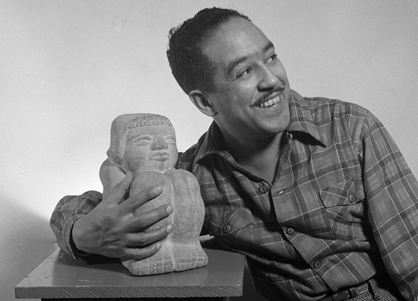 Poet Langston Hughes, with one arm around a small statue of a seated man.
