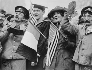 Four people in a crowd wearing uniforms. One man plays a concertina, while a woman in a Red Cross uniform holds two flags.