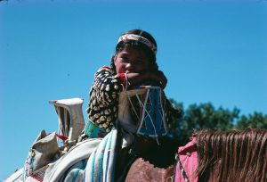 A girl wearing a beaded shirt sits on a horse with an Indian style saddle decorated with beads and a blanket decorated with beads.