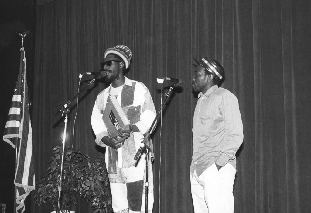 Two British African men standing on a stage at microphones