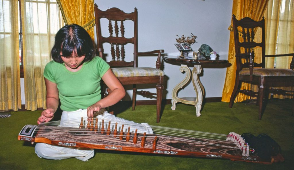 A woman sitting on the floor playing a long zither type instrument on her lap.
