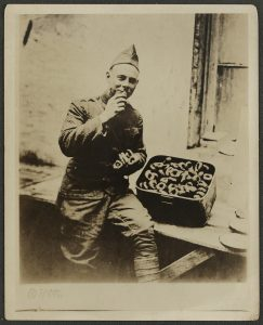 Dennis J. Sullivan eating donuts provided by the Salvation Army in France.