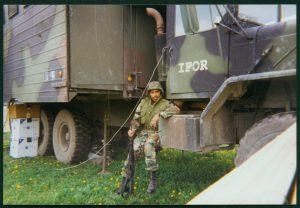 Charles Evert Pulliam in Army uniform leaning on information truck in Bosnia.