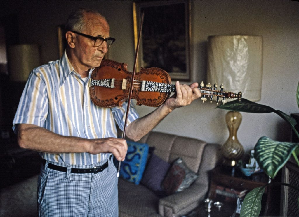 A man plays a Hardanger fiddle (a Norwegian variant of the violin) while standing up.