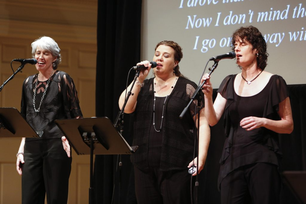 Three women dressed in black sing into microphones.