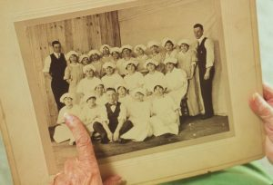 An old photo of a group of people held in a woman's hands. She is pointing at one of the women in the picture.