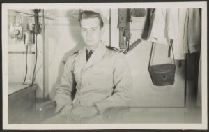 Black and white photograph of Bill Boehne sitting in a chair in his Navy uniform. A desk is to his left, and clothes hang above him.