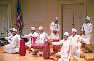 A group of men in traditional white monastic dress kneel on the floor as they perform a dance. Each holds a drum.