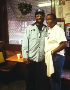 An African American man and woman posing in a restaurant.