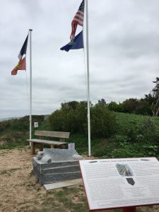 The Charles Shay Indian Memorial: a wooden bench is flanked by flags (unidentified) waving in the wind. A explanatory placard is in the foreground, and a turtle statue is in the middle ground.