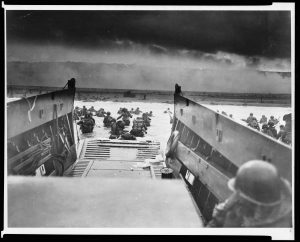 Black and white photograph of soldiers departing a landing craft into the ocean.
