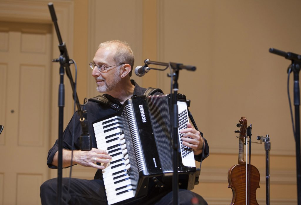 Michael Alpert, seated, plays the accordion on stage.