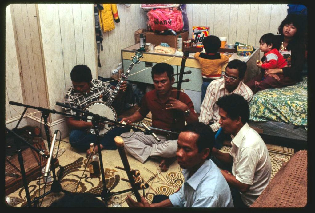 Color photograph depicting a recording session of Cambodian musicans in the home of Sorn Veuk. Lowell, Massachusetts in 1987. Photo by David Taylor.