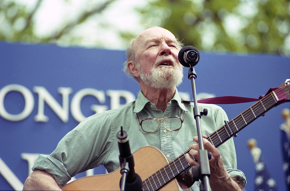 Pete Seeger with guitar singing into a microphone