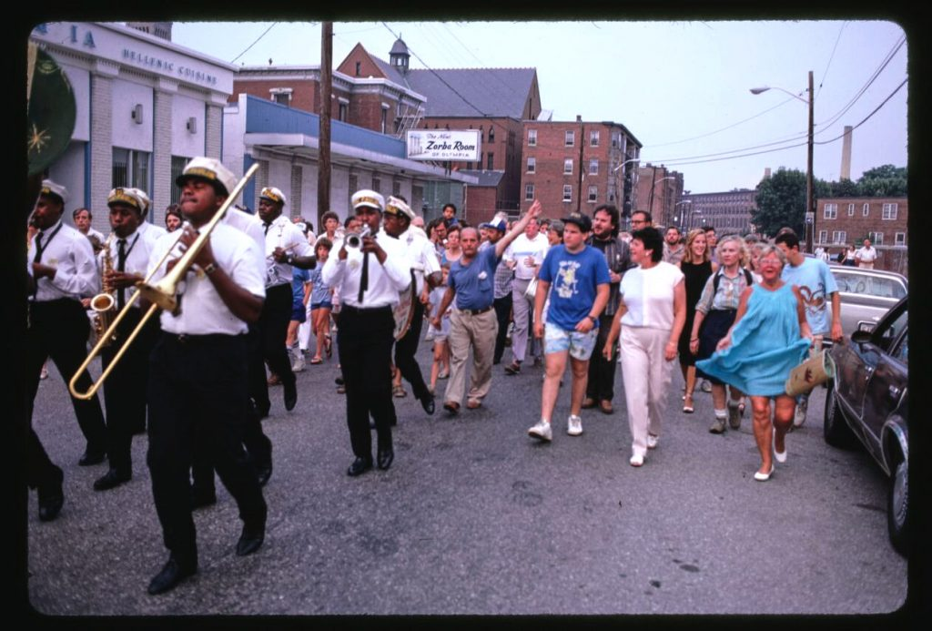 "Image showing Doc Poulin's Jazz band leading a ""jazz march"" in the strees of Lowell during the National Folk Festival in 1987. Photo taken by Douglas DeNatale.."