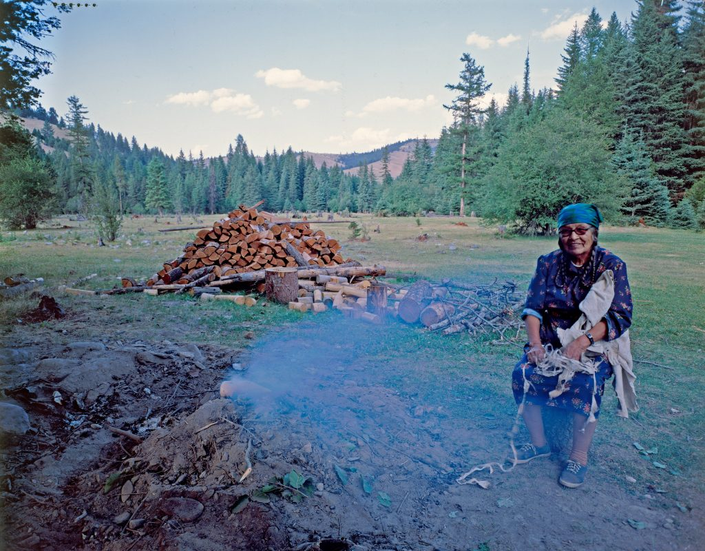 Agnes Vanderburg sits on a log next to a pit from which smoke is rising. A large woodpile is behind her, and the forest and mountains visible in the background.