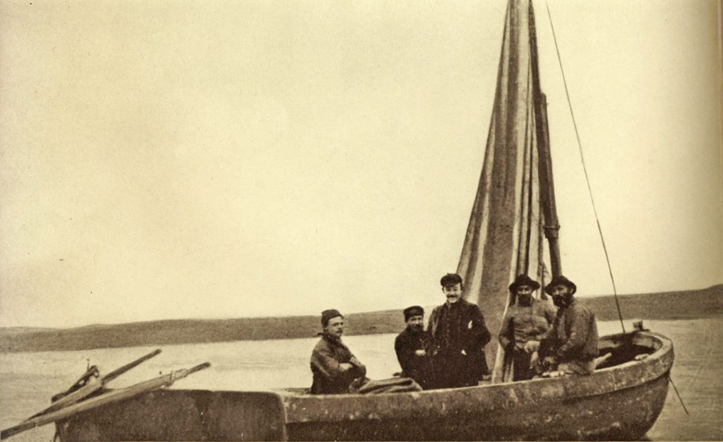 Sepia photo of five men standing in a single-masted sailboat.