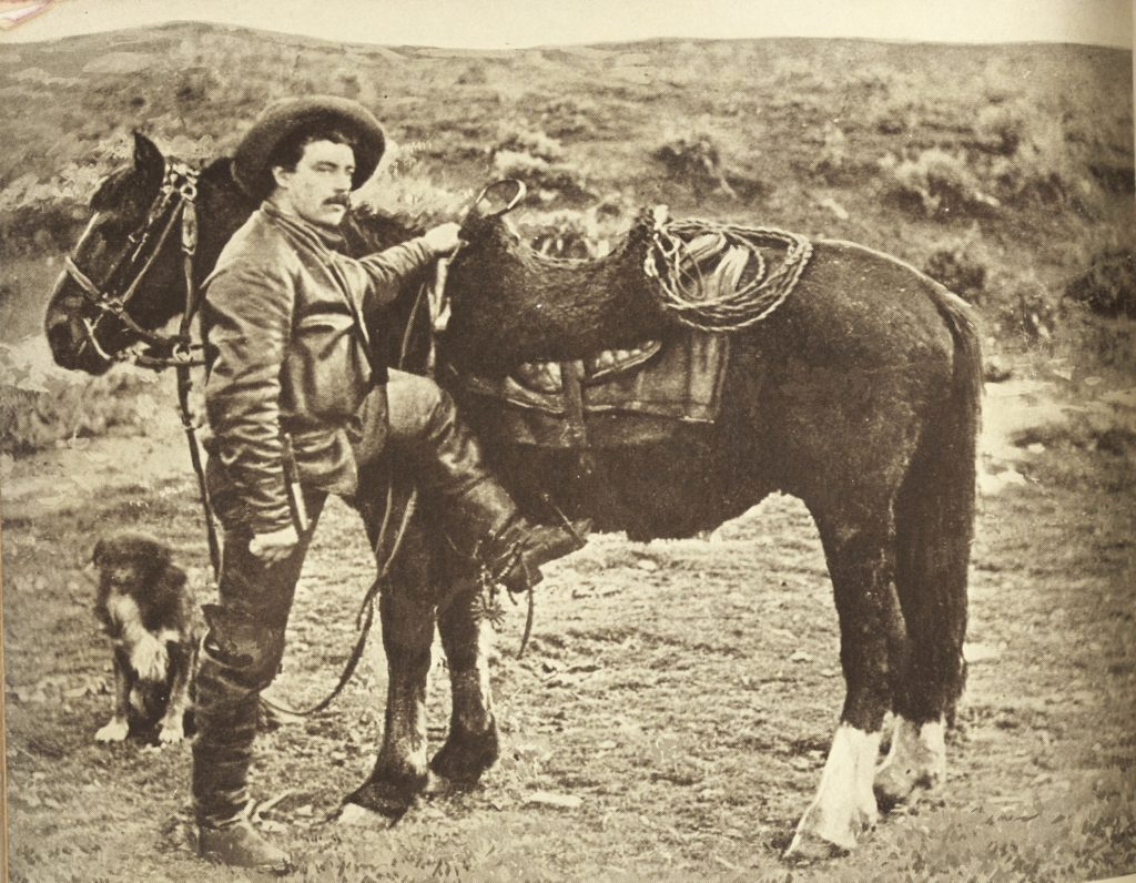 Sepia photo shows Charles J. Finger dressed as a cowboy, holding his horse's saddle and with his foot in the stirrup, ready to mount.
