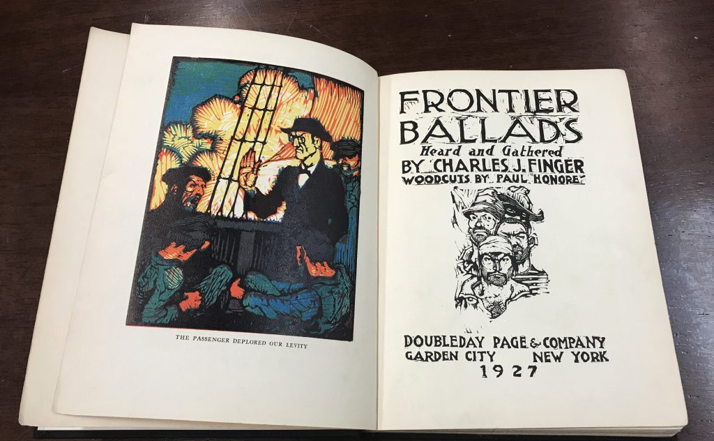 A book is open to its title page, showing an artwork of sailors on the deck of a ship on the left page, and the title Frontier Ballads Heard and Gathered by Charles J Finger, Woodcuts by Paul Honore, Doubleday Page & Company Garden City New York on the right page.