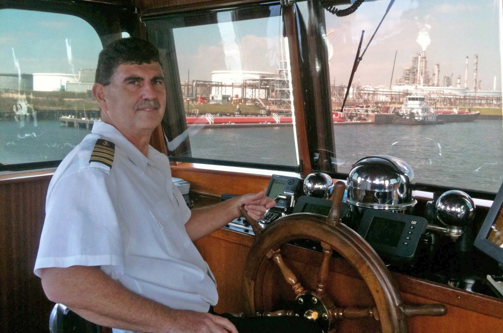 Photograph of Captain Doug Mims in the wheelhouse on the M/V SAM HOUSTON, 2012-09-11. Mims has his hands on a wooden ship's wheel and beyond through the window are other ships in the channel.