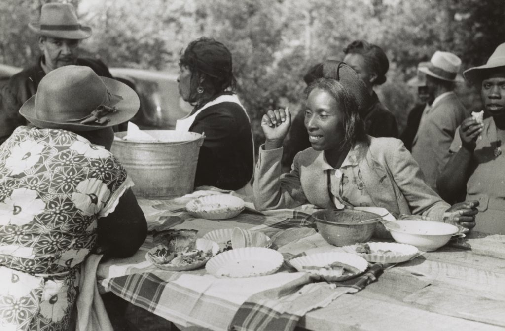 Photograph shows African American women talking across picnic table covered with food. In the background are other women and men.