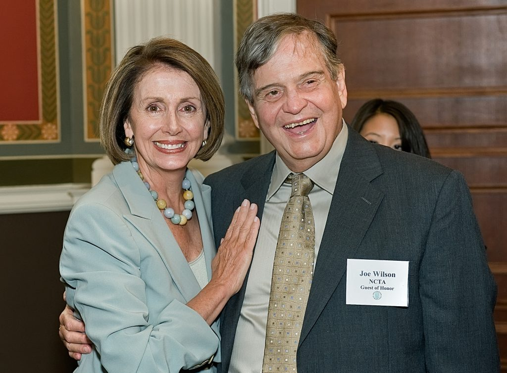 Half-length portrait of Speaker of the House Nancy Pelosi with an arm around folklorist Joe Wilson.