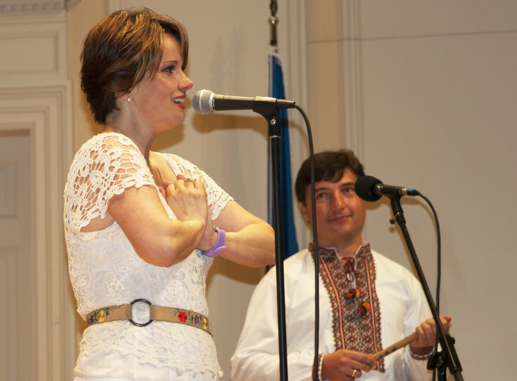 Woman, standing, sings into a microphone. A man looks on admiringly.