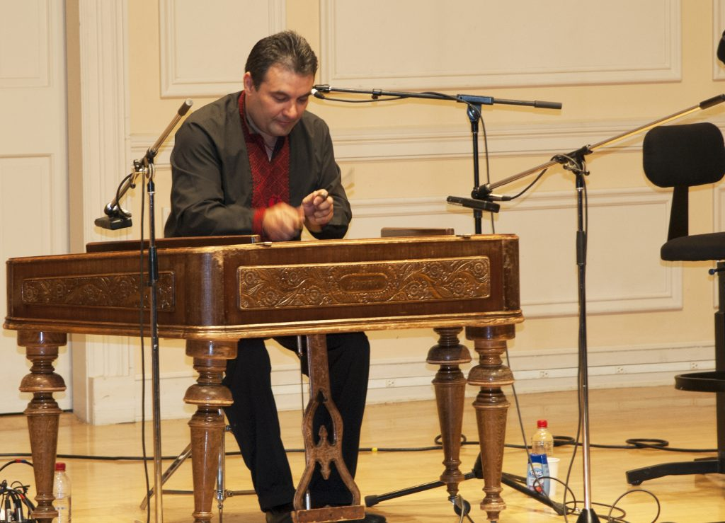 Man, seated, plays hammered dulcimer on a stage.