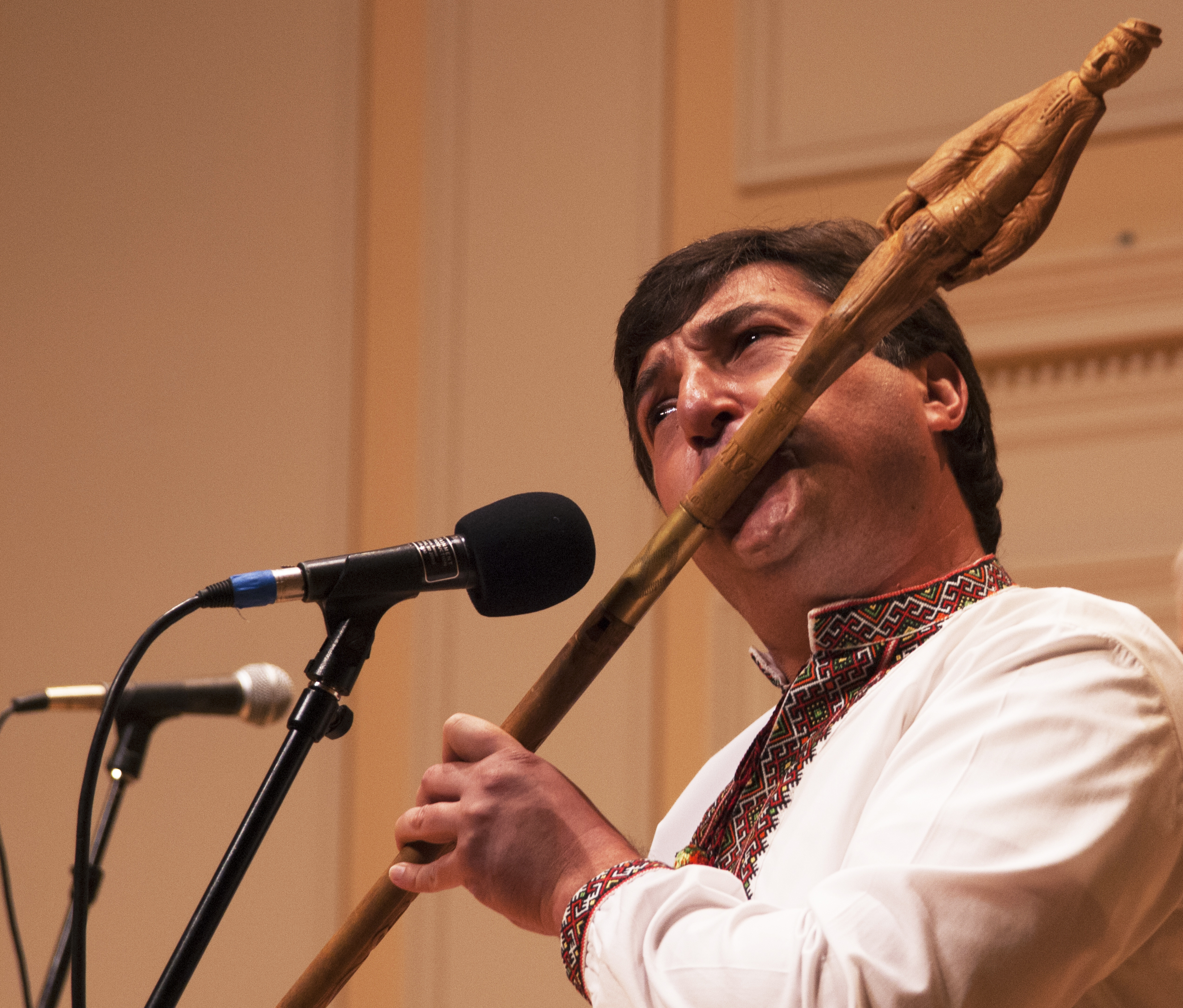 Man plays a long flute. The end of the flute is carved to represent a man wearing Ukrainian rural clothing.