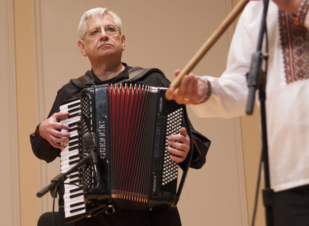Man, seated, plays a large piano accordion on a stage.