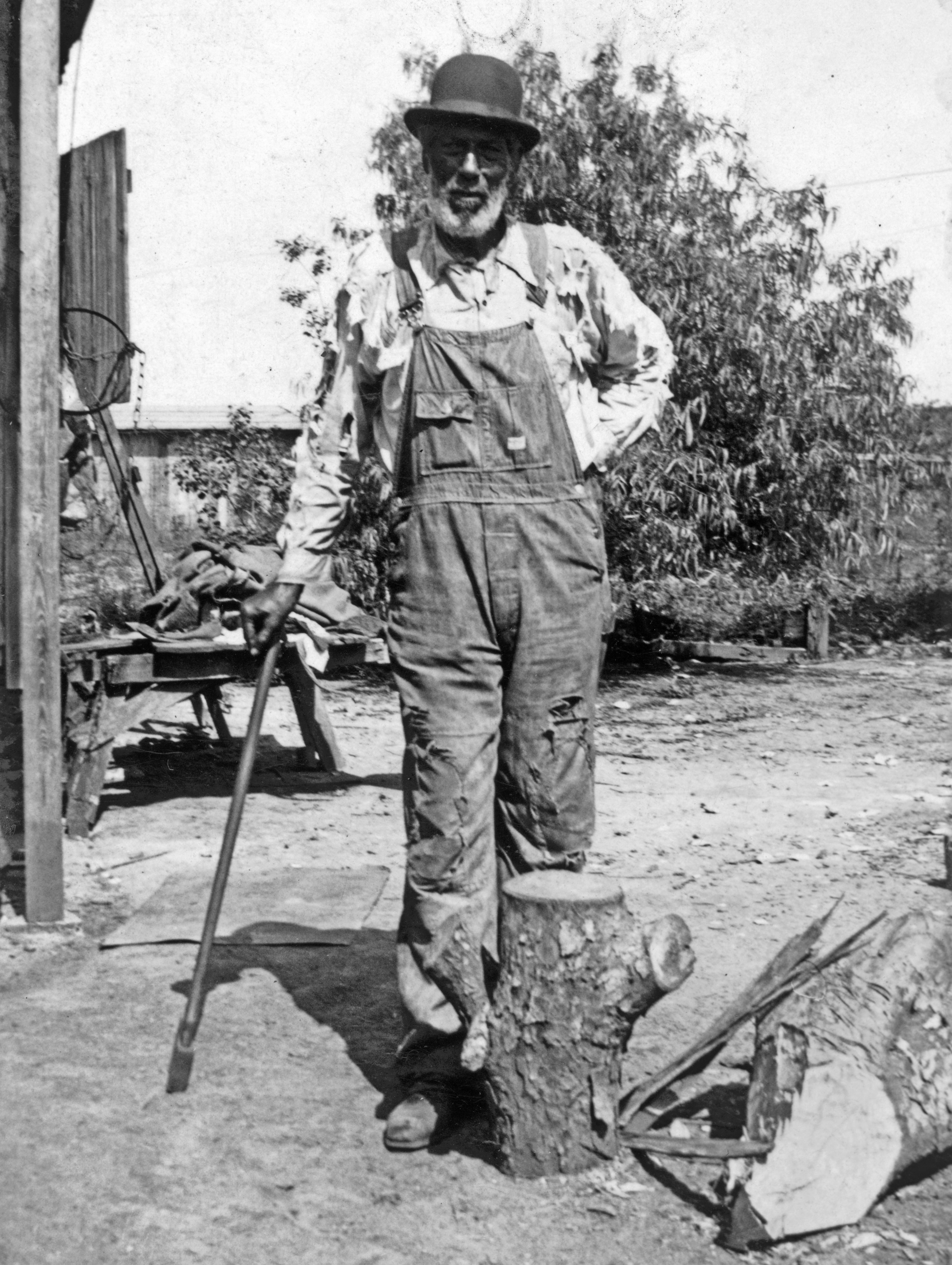 An elderly African American man in overalls, a work shirt, and a bowler hat, leaning on a cane.