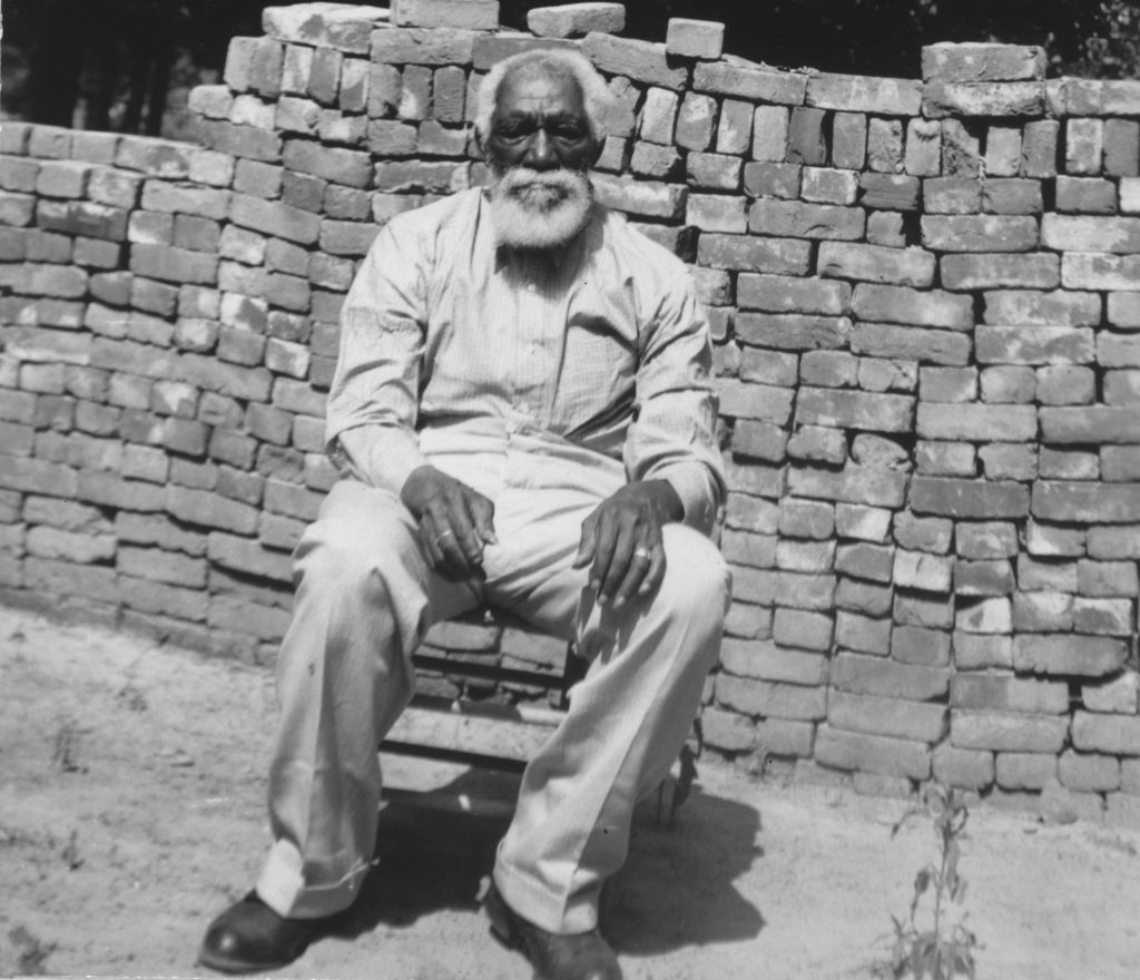 An elderly African American man with a white beard sits in a chair.