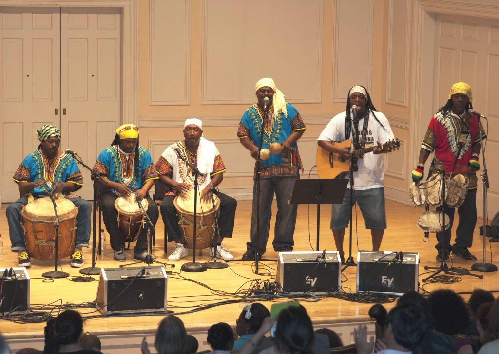 Six men playing drums, maracas, turtle shells, and a guitar.
