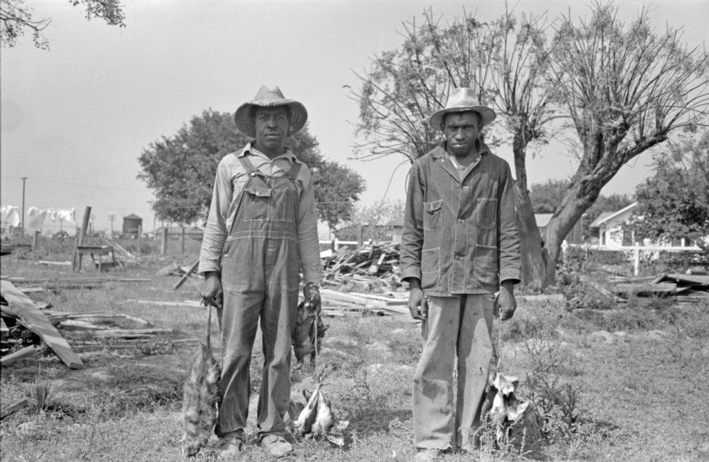 Two African American men in work clothes and broad-brimmed hats. One holds an opossum by the tail in his right hand and birds in his left hand.