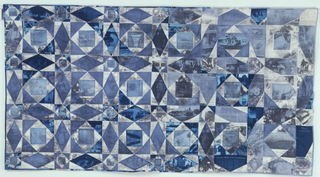 A rectangular quilt in blue, gray, and white patchwork. The pieces are printed with text and images, described in the text of this blog.