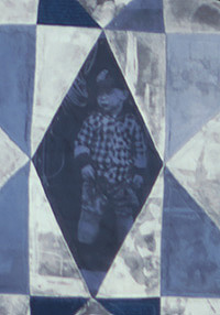 A section of the quilt showing a diamond shape piece printed with the picture of a small boy wearing a plaid shirt and a cap.