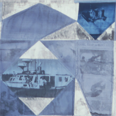 A section of a quilt in blues and grays printed with photos and news clippings.