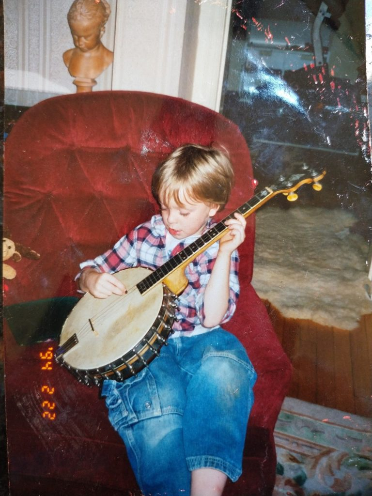 Young boy playing a banjo, seated in a red reclining chair.