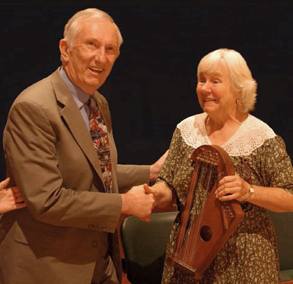 A man shakes hands with a woman. The woman is holding a stringed instrument.