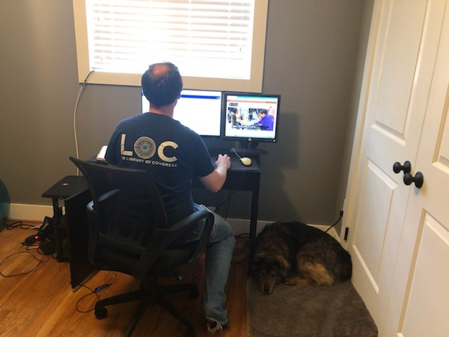 Andrew Huber seated at computer with his back to the camera, and his dog resting on the floor beside him. Huber is weraing a black Library of Congress t-shirt and blue jeans.