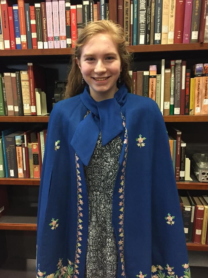A young woman wearing an embroidered cloak stands in front of a bookcase.